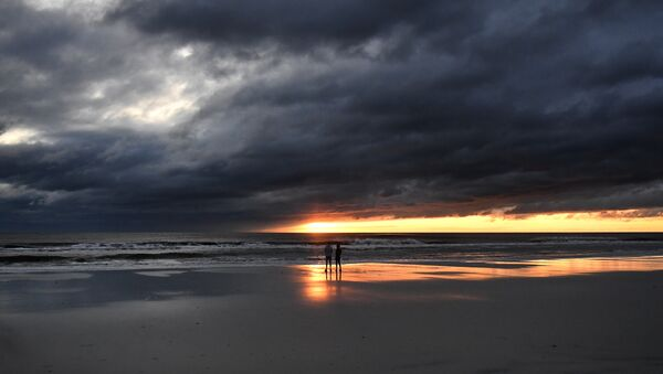 A couple watch the sunrise in Jacksonville Beach, Florida, on October 8, 2016, after Hurricane Matthew passed the area - Sputnik International