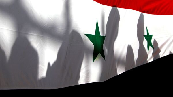 The shadows of people on a Syrian national flag are seen while they attend a peace march to mark International Day of Peace in Damascus. - Sputnik International
