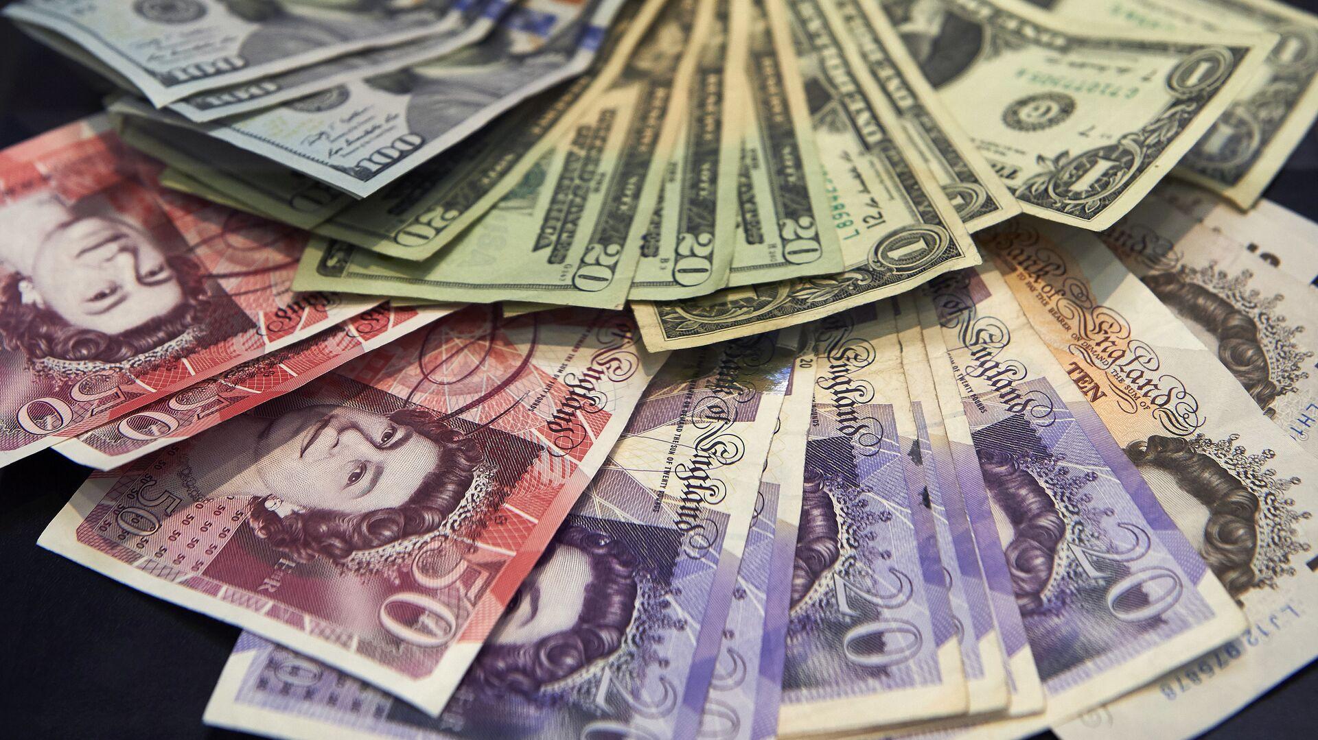 A cashier displays multiple denomination US dollar and British pound Sterling bank notes - Sputnik International, 1920, 28.09.2021