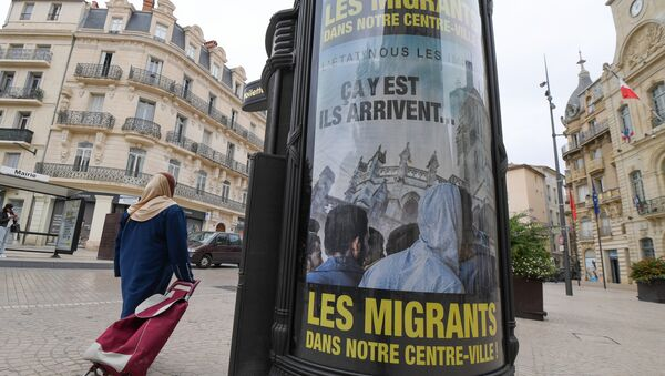A woman walks by a poster reading They are coming, Migrants in our town centre in a street of Beziers, southern France, on October 12, 2016. - Sputnik International