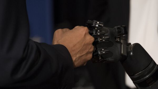 US President Barack Obama (L) fist bumps with the robotic arm of neuro interface patient Nathan Copeland (R) as he tours innovation projects at the White House Frontiers Conference at the University of Pittsburg in Pittsburg, PA, October 13, 2016. - Sputnik International