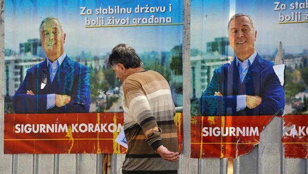 A man walks by election posters of Montenegrin Prime Minister Milo Djukanovic in Podgorica on October 14, 2016 - Sputnik International