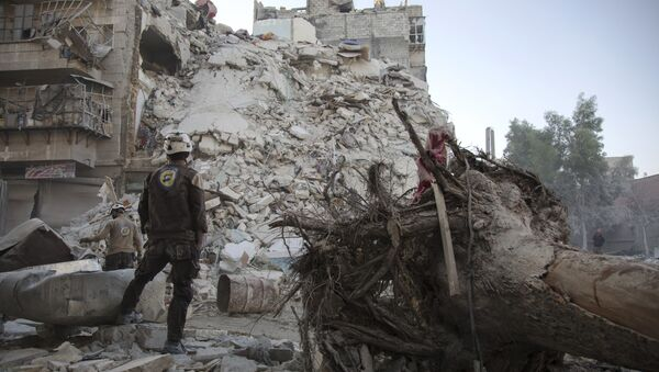 A member of the Syrian Civil Defence, known as the White Helmets, stands amid the rubble of a destroyed building during a rescue operation following reported air strikes in the rebel-held Qatarji neighbourhood of the northern city of Aleppo, on October 17, 2016 - Sputnik International