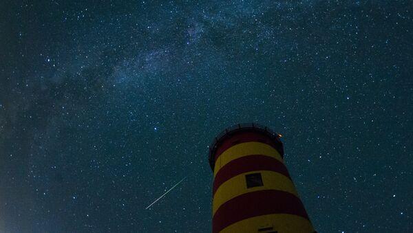 A falling star crosses the night sky behind the lighthouse in Pilsum, northwestern Germany - Sputnik International