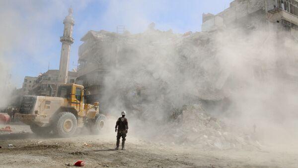 A Civil Defence member stands as a front loader removes debris after an air strike Sunday in the rebel-held besieged al-Qaterji neighbourhood of Aleppo, Syria October 17, 2016. - Sputnik International