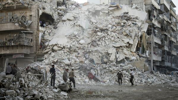 Members of the Syrian Civil Defence, known as the White Helmets, search for victims amid the rubble of a destroyed building following reported air strikes in the rebel-held Qatarji neighbourhood of the northern city of Aleppo, on October 17, 2016. - Sputnik International