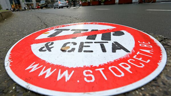 A cyclist rides past a placard reading  STOP TTIP CETA outside the EU Council headquarters ahead of a European Union leaders summit in Brussels, Belgium October 20, 2016. - Sputnik International