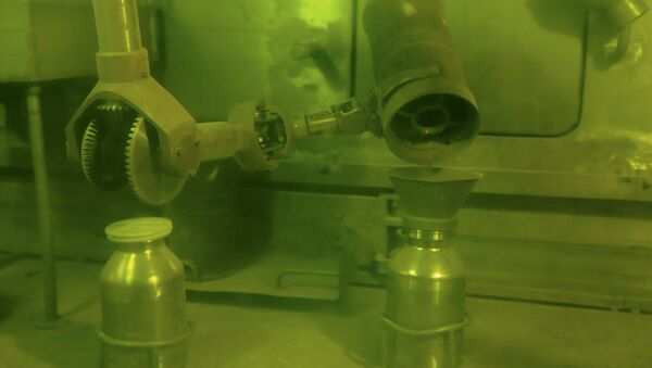 Operator putting plutonium dioxide powder in a container for storage and processing using handler. - Sputnik International