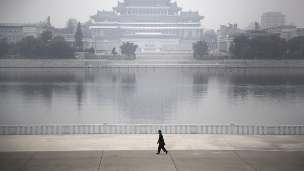 A North Korean man makes his way along the Taedong River where the Kim Il Sung Square and the Grand People's Study House are seen on the other side in Pyongyang, North Korea - Sputnik International