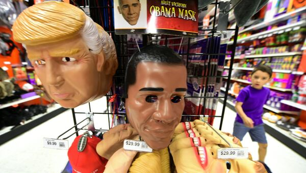 A child walks past a display of masks of US President Barack Obama, and presidential hopefuls Donald Trump and Hillary Clinton, for sale at a shop selling Halloween items in Alhambra, California on October 21, 2016 - Sputnik International
