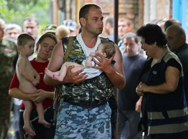 A Special Forces soldier carries a baby after a school was liberated from militants in Beslan, North Ossetia. The Beslan school siege started on September 1, 2004, and lasted three days. Over 1,100 people were taken hostage, including 777 children; at least 385 people died in Russia's worst ever terrorist attack. - Sputnik International
