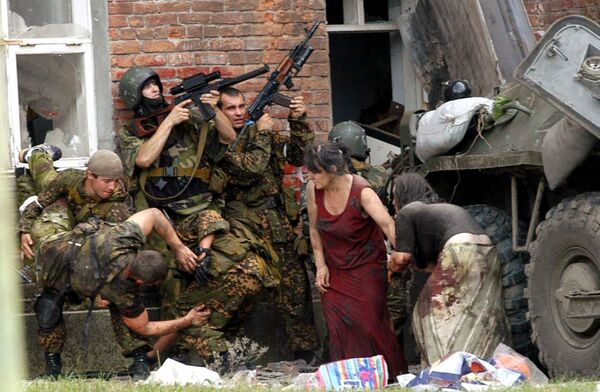 A Russian special police soldier (L) carries an injured colleague as two soldiers and two women take cover behind the APC during the Beslan School rescue operation, northern Ossetia, September 3, 2004. - Sputnik International