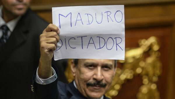 A Venezuelan opposition deputy holds up a sing reading  Maduro dictator during an extraoridinary session of the National Assembly, in Caracas on October 23, 2016 - Sputnik International