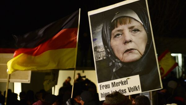A protestor holds a poster with an image of German Chancellor Angela Merkel during a rally of the group Patriotic Europeans against the Islamization of the West, or PEGIDA, in Dresden, Germany. file photo - Sputnik International