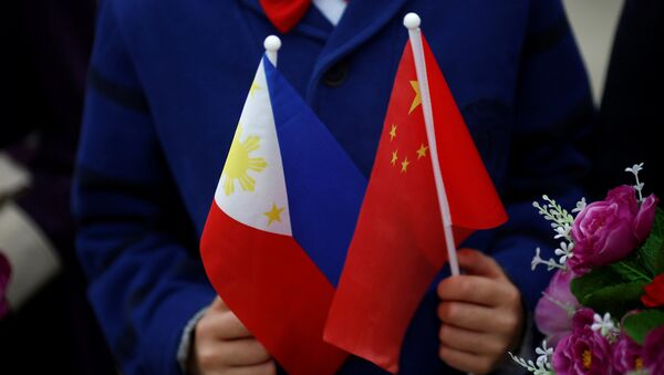 Children hold plastic flowers, national flags of China and the Philippines before President of the Philippines Rodrigo Duterte and China's President Xi Jinping attend a welcoming ceremony at the Great Hall of the People in Beijing, China, October 20, 2016 - Sputnik International