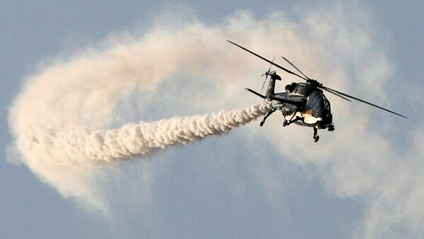 This handout photograph released by the Ministry of Defence on February 20, 2013, shows a HAL Black Tiger Light Combat Helicopter (LCH) performing a flypast during a full dress rehearsal for the Indian Air Force's Iron Fist 2013 military exercicse in Pokhran, near Jaisalmer in India's Rajasthan state, on February 19, 2013 - Sputnik International