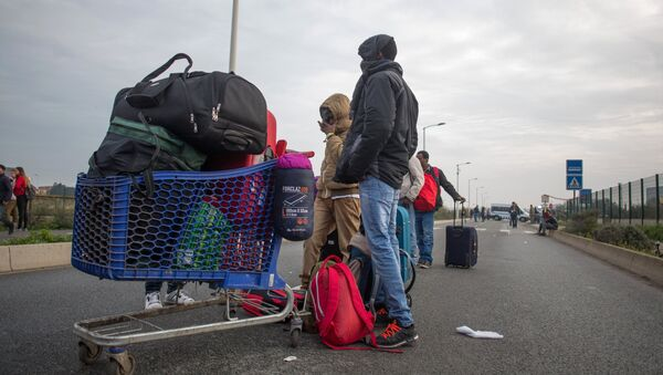 Refugees at a special center for the relocation of migrants (Centres d'Accueil at d'Orientation) near a refugee camp in Calais, France. - Sputnik International