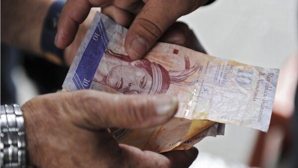 A man receives Venezuelan currency bills in Caracas on November 30, 2011. - Sputnik International