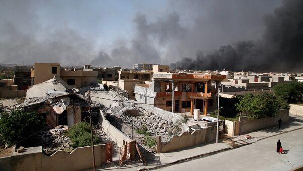 People walk along a street as smoke rises near Qayyarah, south of Mosul, Iraq - Sputnik International