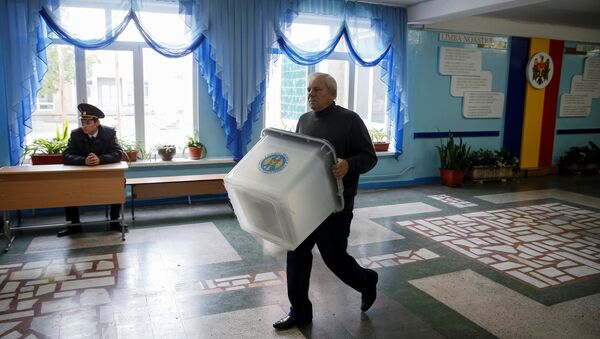 A member of a local electoral commission carries a ballot box at a polling station ahead of the presidential election in Chisinau, Moldova, October 29, 2016. - Sputnik International