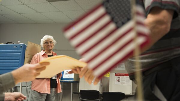 An election official watches as a man takes a ballot at an in-person absentee voting station in Fairfax, Virginia on October 12, 2016 - Sputnik International