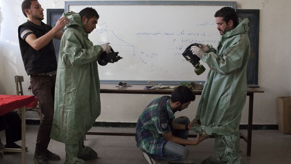 An Aleppo University student, shows Syrian citizens hows to put protective gear as he instructs them with rudimentary means of how to respond to a chemical attack, in the northern Syrian city of Aleppo (File) - Sputnik International