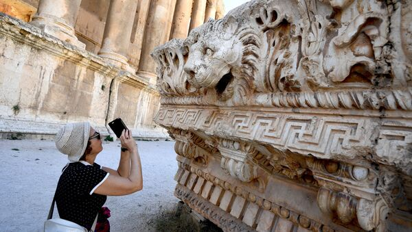 A visitor takes pictures of a bas-relief with heads of lions from the roof of the Temple of Jupiter in a temple complex of Baalbek, Lebanon - Sputnik International