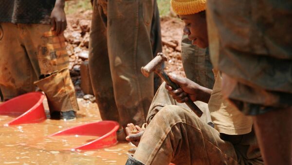 An unidentified miner sifts through sand and smashed rocks looking for gold at the town of Mongbwalu, Congo (File) - Sputnik International