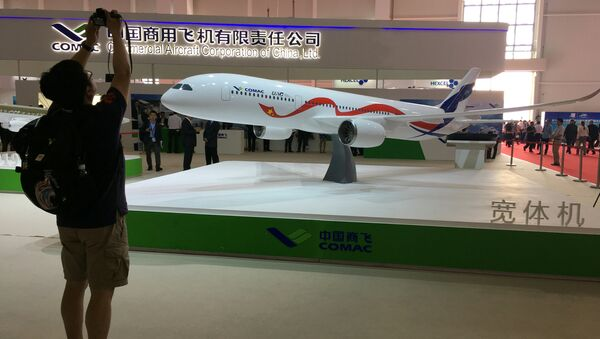 A man takes picture of the model of a widebody jet, which is planned to be developed by Commercial Aircraft Corporation of China (COMAC) and Russia's United Aircraft Corporation (UAC) at an air show, the China International Aviation and Aerospace Exhibition, in Zhuhai, Guangdong Province, China, November 2, 2016 - Sputnik International
