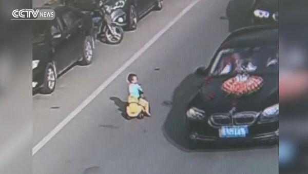 Kid drives toy car through traffic on busy road - Sputnik International