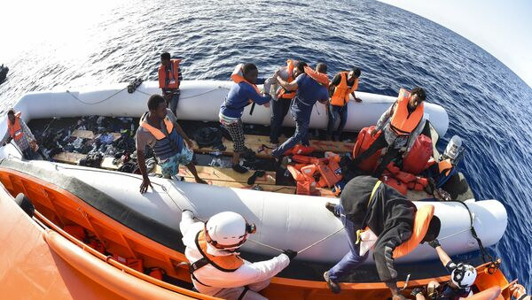 Men evacuate a rubber boat with the help of the crew of the Topaz Responder ship run by Maltese NGO Moas and the Italian Red Cross during a rescue operation of Migrants and refugees on November 3, 2016, off the Libyan coast in the Mediterranean Sea - Sputnik International