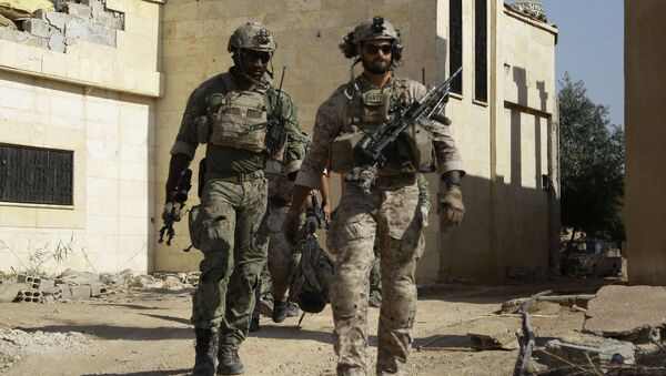 Armed men in uniform identified by Syrian Democratic forces as US special operations forces walk in the village of Fatisah in the northern Syrian province of Raqa on May 25, 2016 - Sputnik International