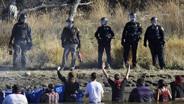 Dozens of protestors demonstrating against the expansion of the Dakota Access Pipeline wade in cold creek waters confronting local police, as remnants of pepper spray waft over the crowd near Cannon Ball, N.D., Wednesday, Nov. 2, 2016. - Sputnik International