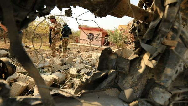 Iraqi security forces walk amidst rubble near a wreckage of a vehicle that was destroyed during clashes in Hammam al-Alil, south of Mosul, during an operation to attack Daesh terrorists in Mosul, Iraq. File photo - Sputnik International