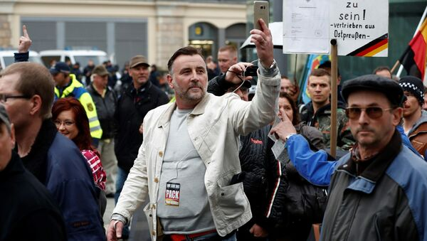 Lutz Bachmann (C), co-founder of the Pegida movement (Patriotic Europeans Against the Islamisation of the Occident), documents with his mobile phone as he takes part in a protest against German Chancellor Angela Merkel and her policy, on October 3, 2016, the German Unity Day, in Dresden, eastern Germany - Sputnik International