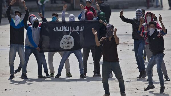 Kashmiri Muslim protesters hold a flag of Islamic State as they shout anti-India slogans during a protest in Srinagar, Indian controlled Kashmir, Friday, April 8, 2016 - Sputnik International