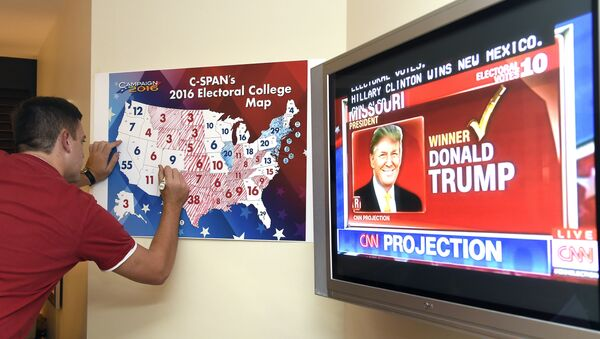 Jake Krupa colors in an electoral map as states projected for Republican presidential candidate Donald Trump or Democratic Presidential candidate Hillary Clinton at an election watching party in Coconut Grove, Florida, on November 8, 2016 - Sputnik International