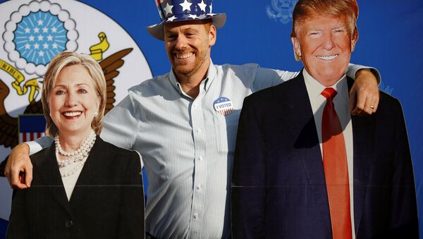 A man poses for a picture with the cardboard cutouts of US presidential nominees Hillary Clinton (L) and Donald Trump, at an election event hosted at the US ambassador's residence in Kathmandu, Nepal November 9, 2016. - Sputnik International