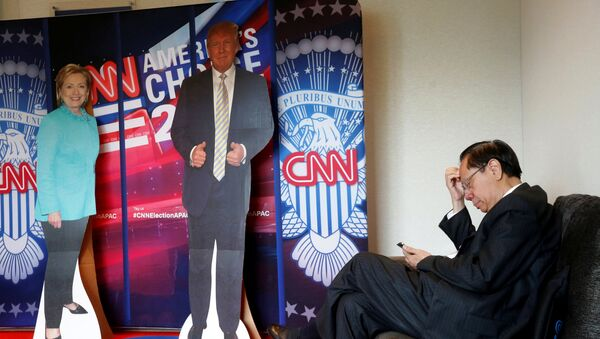 A man checks his smartphone beside cardboard cutouts of U.S. presidential candidates Hillary Clinton (L) and Donald Trump, at an event held by the American Chamber of Commerce in Hong Kong, China November 9, 2016. - Sputnik International