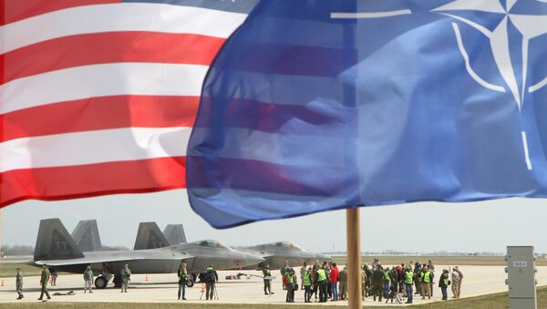 The US and The NATO flag flie in front of two US Air Force F-22 Raptor fighter aircrafts at the Air Base of the Lithuanian Armed Forces in Šiauliai, Lithuania, on April 27, 2016. - Sputnik International