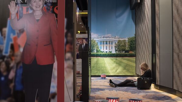 A woman sits on the floor behind a cut-outs of US presidential nominees Hillary Clinton and Donald Trump at an election event organised by the US embassy, at a hotel in Seoul on November 9, 2016 - Sputnik International