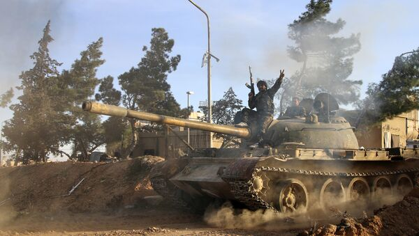 Volunteer fighter with the Syrian Government forces sits atop a tank in the province of Raqqa, Syria (File) - Sputnik International