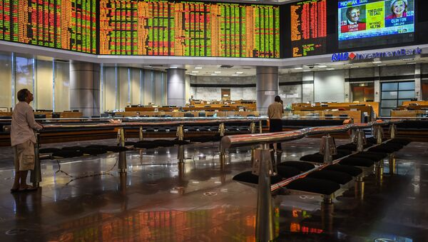Traders monitor electronic boards showing stock movements during the final day of the US presidential election at a private stock exchange in Kuala Lumpur on November 9, 2016 - Sputnik International