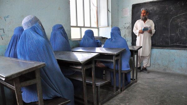 Afghan schoolgirls clad in burqas pay attention to their male teacher in the outskirts of Herat province on June 26, 2011 - Sputnik International
