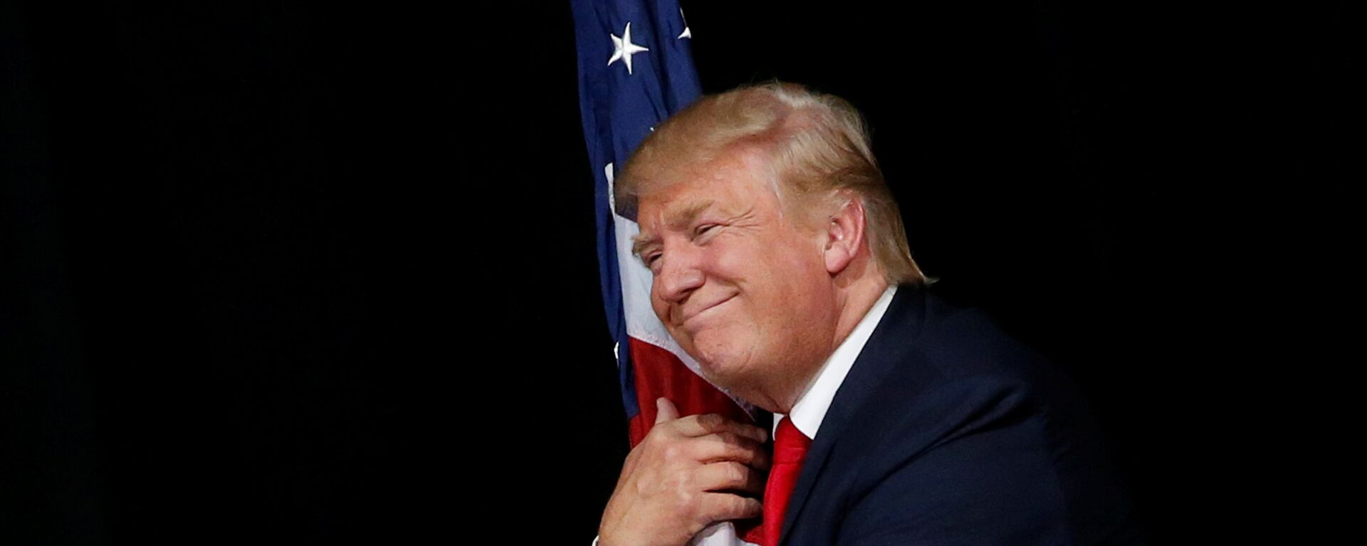 Donald Trump hugs a U.S. flag as he comes onstage to rally with supporters in Tampa, Florida, U.S. October 24, 2016 - Sputnik International, 1920, 12.09.2021