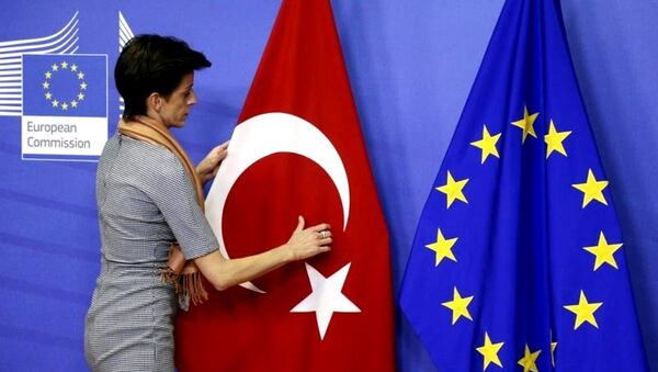 A woman adjusts the Turkish flag next to the European Union flag before the arrival of Turkish Prime Minister Ahmet Davutoglu (unseen) at the EU Commission headquarters in Brussels January 15, 2015. - Sputnik International