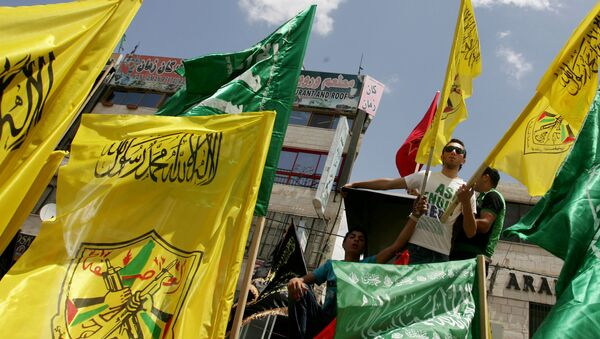 Palestinian supporters of Hamas Islamist movement and of Fatah party wave their faction's flags during a rally to support the Palestinian political unity deal, in the West Bank city of Jenin. (File) - Sputnik International