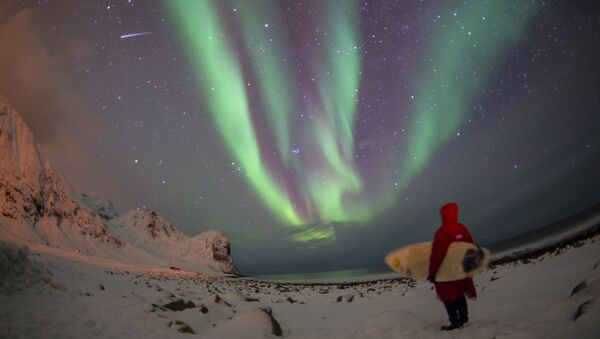 A surfer looks at northern lights ( aurora borealis ) at the snow covered beach of Unstad, on Lofoten Island, Arctic Circle, on March 9, 2016 - Sputnik International