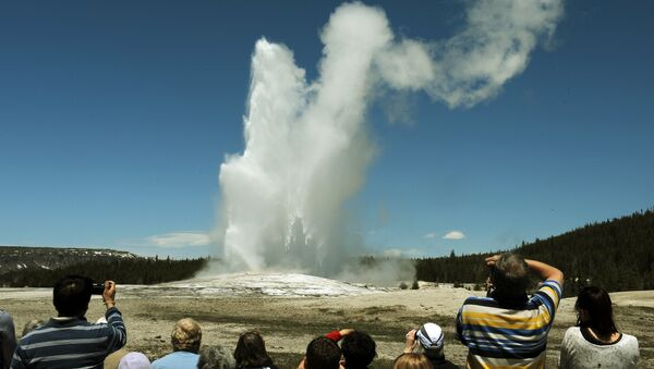 Tourists watch the 'Old Faithful' geyser which erupts on average every 90 minutes in the Yellowstone National Park, Wyoming on June 1, 2011 - Sputnik International