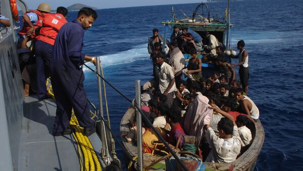 Members of the Indian coastguard rescue illegal Bangladeshi migrants in their trawler after they were sighted by the Coast Guard Aircraft off Chidiyatapu Island in the southern Andaman Islands on January 8, 2009 - Sputnik International